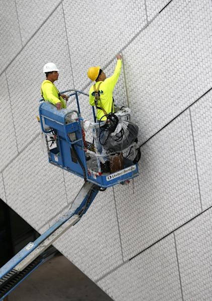 In this Thursday, Dec. 8, 2016 photo, workers are seen during construction at the Patricia and Phillip Frost Museum of Science in Miami. Rising next to Miami's spiffy new bayside art museum is a $305 million science museum that, like South Florida, is focused in large part on water: its centerpiece is a 500,000-gallon aquarium that will feature sharks, tuna, mahi-mahi and even sea turtles, with other smaller tanks for corals and other sea life. The Frost Science Museum, scheduled to open this spring. (AP Photo/Wilfredo Lee)