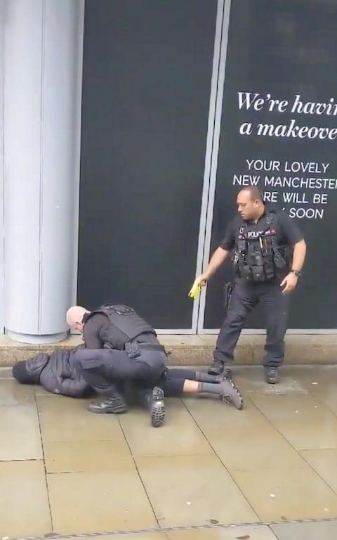 A police officer points a taser while the other holds a man down outside the Arndale shopping center, where several people were stabbed - Credit: JOHN GREENHALGH