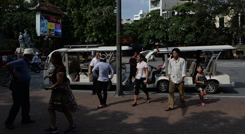 A group of Taiwanese tourists get off two electrical cars in Hanoi downtown on July 16, 2014 (AFP Photo/Hoang Dinh Nam)