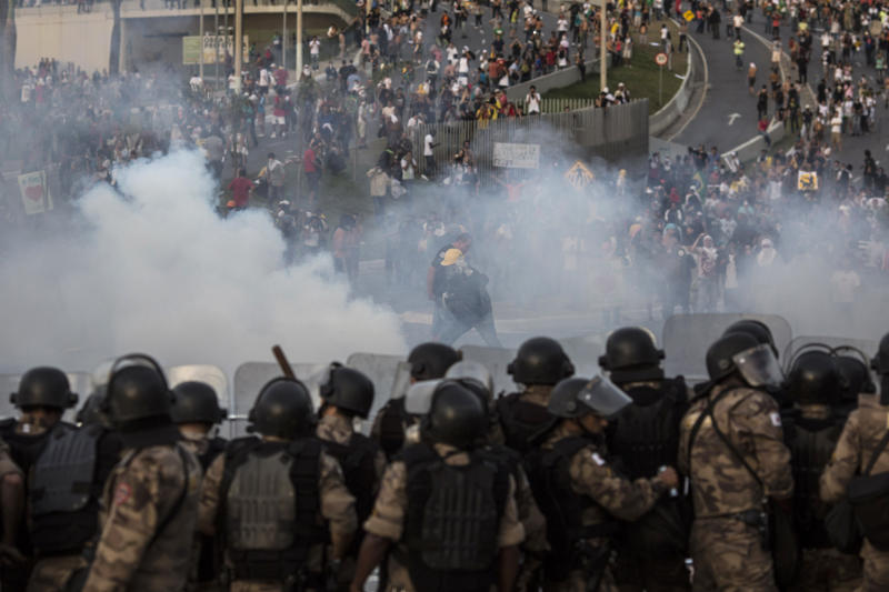 People run away from tear gas during a protest outside the Minerao stadium during a soccer Confederations Cup match between Japan and Mexico in Belo Horizonte, Brazil, Saturday, June 22, 2013. Thousands of anti-government demonstrators again took to streets in several Brazilian cities Saturday after the president broke a long silence to promise reforms.(AP Photo/Felipe Dana)