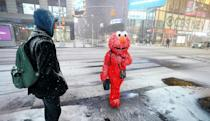 A person in an Elmo costume stands under the snow in Times Square in New York City, December 16, 2020