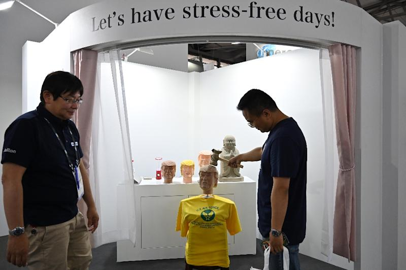 A series of delighted visitors took their turns bashing Trump at the 'stress-relief' station, set up by Japanese tech firm Soliton Systems (AFP Photo/HECTOR RETAMAL)