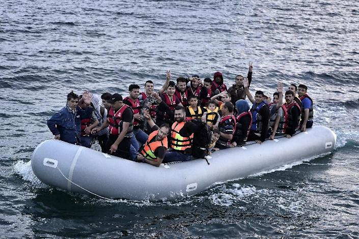 Syrian refugees sit aboard a dinghy heading to the Greek island of Lesbos, early on June 18, 2015 (AFP Photo/Louisa Gouliamaki)