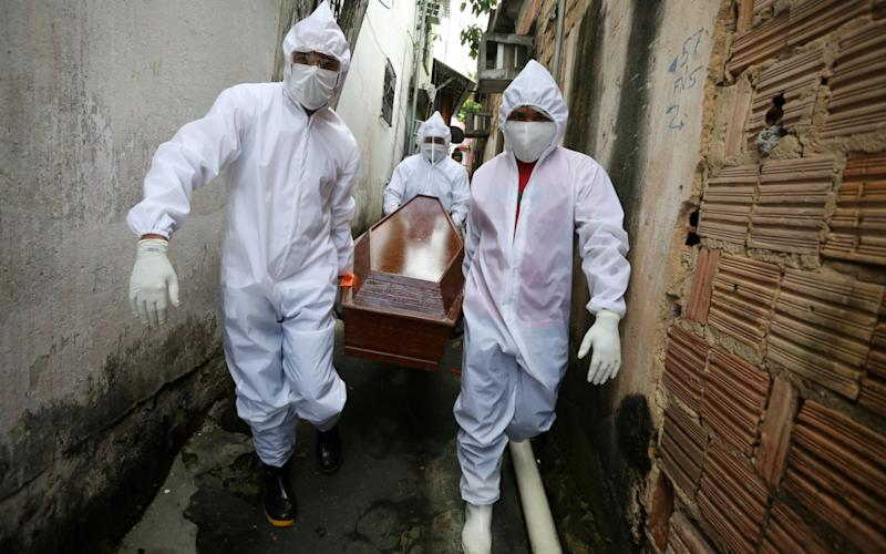 Workers of the Funeral SOS carry a coffin in Manaus