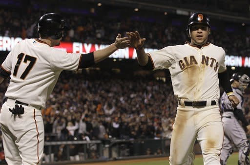 San Francisco Giants' Aubrey Huff (17) and Gregor Blanco celebrate after both scored on Melky Cabrera's double off of Colorado Rockies pitcher Josh Outman during the seventh inning of a baseball game in San Francisco, Tuesday, May 15, 2012. (AP Photo/Jeff Chiu)