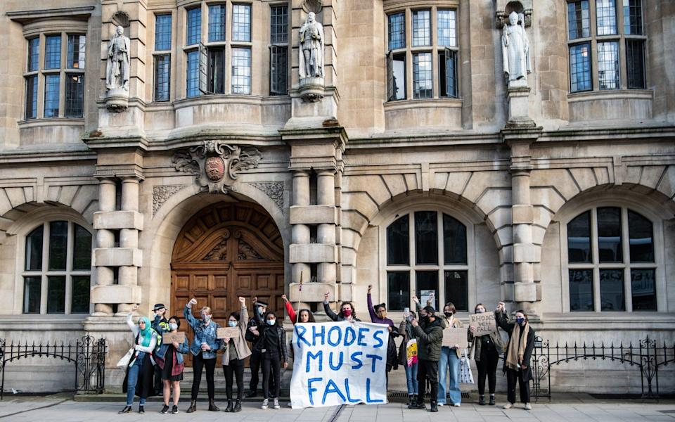Protesters march to Oriel Colleges statue of Cecil Rhodes at the University of Oxford on May 25, 2021 in Oxford, England. - Laurel Chor