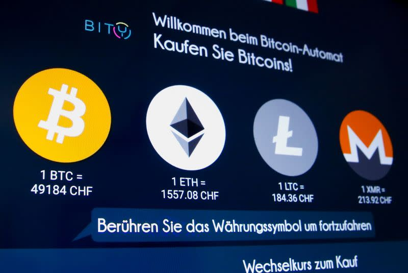 The exchange rates and logos of Bitcoin, Ether, Litecoin and Monero are seen on the display of a cryptocurrency ATM in Zurich