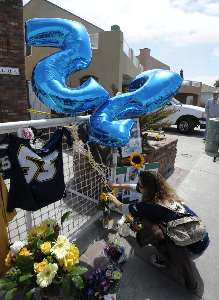 San Diego Chargers fan April Court puts flowers next to balloons with Junior Seau's #55 at a memorial in the driveway of the house of former NFL star Junior Seau Thursday, May 3, 2012, in Oceanside, Calif. Seau's death in Oceanside, in northern San Diego County, stunned the region he represented with almost reckless abandon. (AP Photo/Denis Poroy)