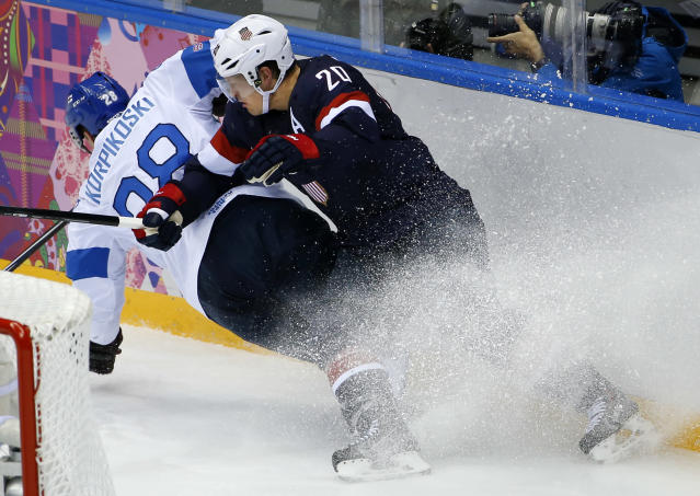 Lauri Korpikoski of Finland (28) and Ryan Suter of the United States (20) crash into the boards during the third period of the men's bronze medal ice hockey game at the 2014 Winter Olympics, Saturday, Feb. 22, 2014, in Sochi, Russia. (AP Photo/Matt Slocum)