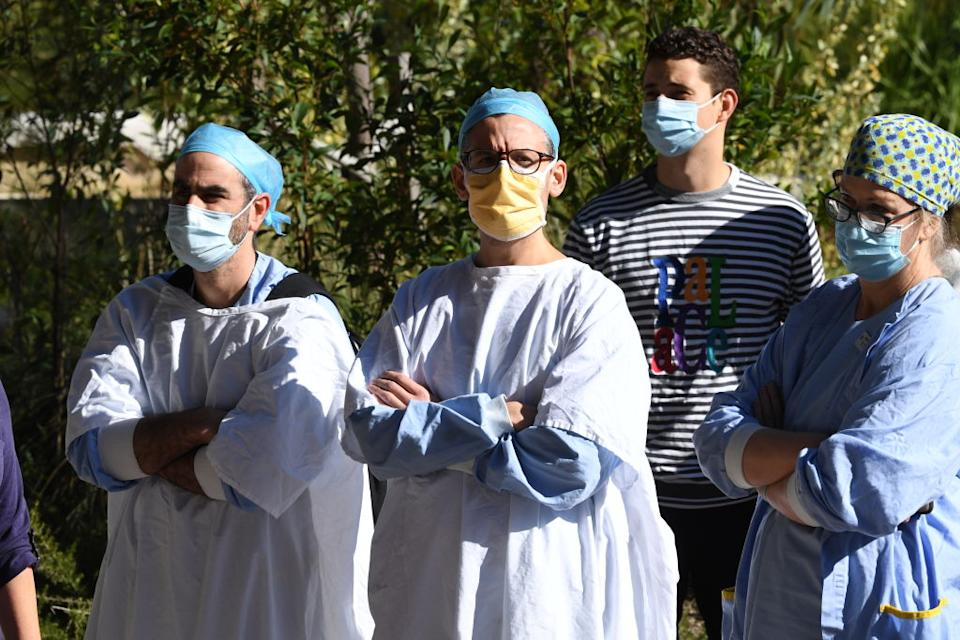 Healthcare workers wearing face masks watch as the Premier of New South Wales, Gladys Berejiklian gives a media conference in St Leonards.
