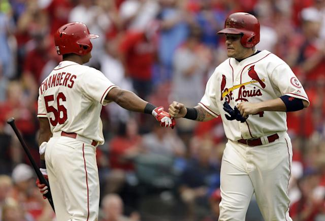 St. Louis Cardinals' Yadier Molina, right, is congratulated by teammate Adron Chambers after scoring on a ground-rule double by Pete Kozma during the third inning of a baseball game against the Chicago Cubs, Saturday, Sept. 28, 2013, in St. Louis. (AP Photo/Jeff Roberson)