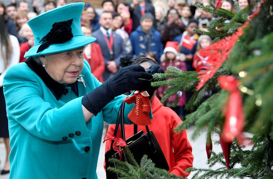 Britain's Queen Elizabeth and Shylah Gordon, aged 8, attach a bauble to a Christmas tree during a visit to children's charity Coram in London, Britain, December 5, 2018. REUTERS/Toby Melville     TPX IMAGES OF THE DAY