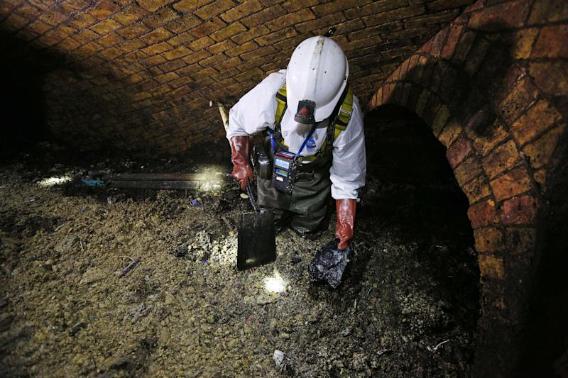 """A """"flusher"""" shovels the fat as he works on a 'fatberg' in the intersection of the Regent Street and Victoria sewer in London. Photo: Getty Images"""
