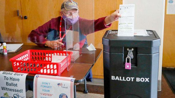 PHOTO: An election worker drops a voter's completed ballot into a ballot box inside City Hall on the first day of in-person early voting in Kenosha, Wisc., Oct. 20, 2020. (Kamil Krzaczynski/AFP via Getty Images)