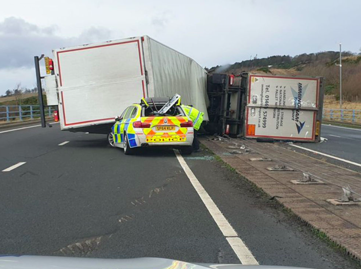 A lorry toppled onto a police car in Scotland during high winds (PA)