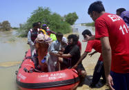 Pakistani rescue workers evacuate villagers from flooded areas of Dadu, a district in Pakistan's southern Sindh province, Sunday, Aug. 9, 2020. Pakistan's disaster management agency said three days of heavy monsoon rains that triggered flash floods have killed dozens of people in various parts of the country. (AP Photo/Pervez Masih)