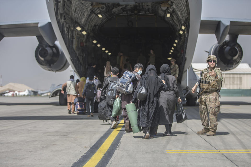 In this image provided by the U.S. Marine Corps, families begin to board a U.S. Air Force Boeing C-17 Globemaster III during an evacuation at Hamid Karzai International Airport in Kabul, Afghanistan, Monday, Aug. 23, 2021. (Sgt. Samuel Ruiz/U.S. Marine Corps via AP)