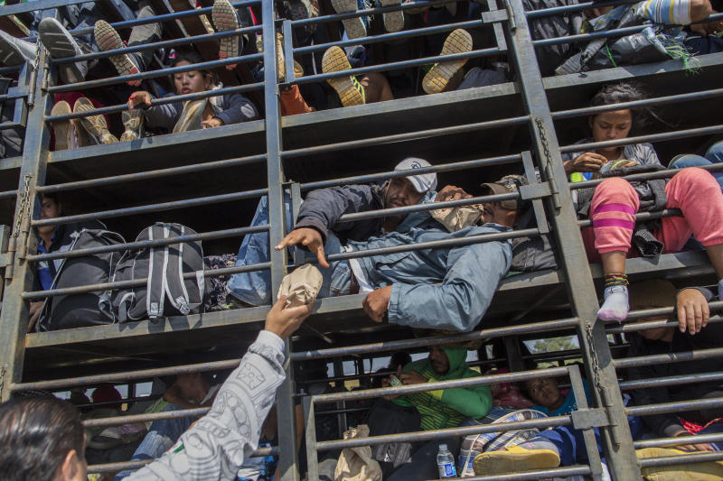 Central American migrants, part of the caravan hoping to reach the U.S. border, receive donated food while traveling on a truck, in Celaya, Mexico, Sunday, Nov. 11, 2018. Local Mexican officials were once again Sunday helping thousands of Central American migrants find rides on the next leg of their journey toward the U.S. border. (AP Photo/Rodrigo Abd)