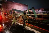 """Soldiers walk by a scene where the roof protecting the """"Casa de las Aguilas"""", part of the ruins of the Templo Mayor archaeological site, collapsed after heavy rain and hail, in Mexico City"""