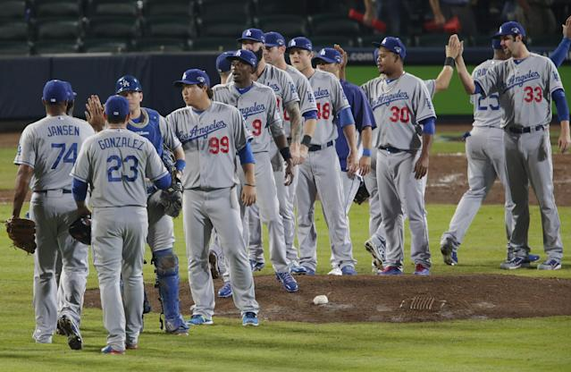 The Los Angeles Dodgers celebrate following a 6-1 win over the Atlanta Braves during Game 1 of the National League Divisional Series, played Thursday, Oct. 3, 2013, in Atlanta. (AP Photo/Dave Martin)