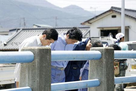 Japan's Prime Minister Shinzo Abe (2nd L) pays a silent tribute to the victims of torrential rain at Nomura town in Seiyo, Ehime Prefecture, Japan, in this photo distributed by Kyodo July 13, 2018. Mandatory credit Kyodo/via REUTERS ATTENTION EDITORS - THIS IMAGE WAS PROVIDED BY A THIRD PARTY. MANDATORY CREDIT. JAPAN OUT.