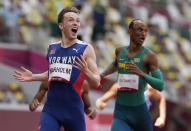 Karsten Warholm, of Norway celebrates as he wins the gold medal in the final of the men's 400-meter hurdles at the 2020 Summer Olympics, Tuesday, Aug. 3, 2021, in Tokyo, Japan. At right is Alison Dos Santos, of Brazil, who took the bronze. (AP Photo/Martin Meissner)