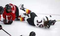 Germany's Kerstin Spielberger, right, falls to the ice after colliding with Canada's Sarah Fillier during the second period of an IIHF women's hockey championships game in Calgary, Alberta, Saturday, Aug. 28, 2021. (Jeff McIntosh/The Canadian Press via AP)