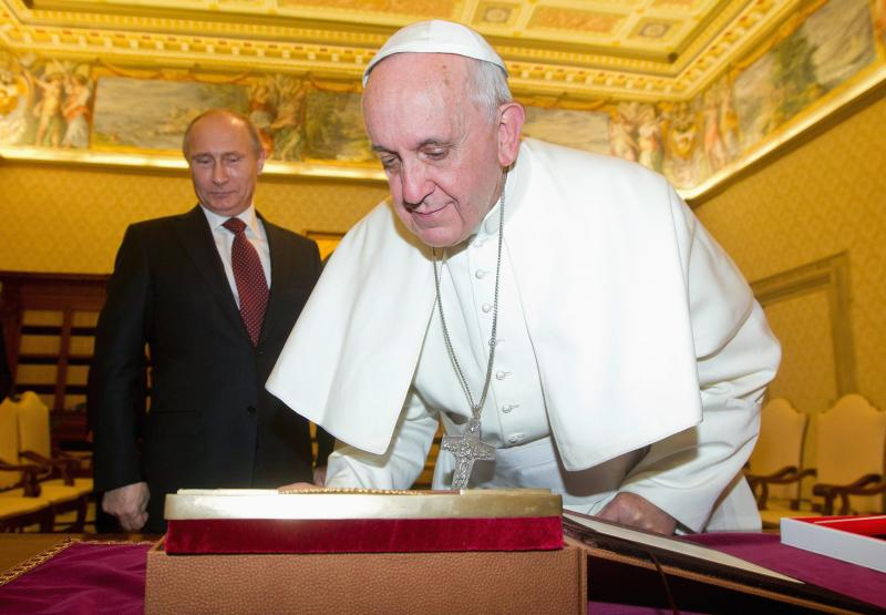 Pope Francis (R) exchanges gifts with Russia's President Vladimir Putin during a private audience at the Vatican, November 25, 2013. REUTERS/Claudio Peri/Pool (VATICAN - Tags: RELIGION POLITICS)