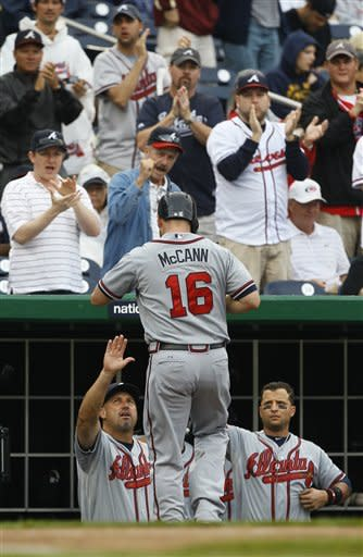 Atlanta Braves Brian McCann, is greeted by manager Fredi Gonzales, left, after hitting a solo home run during the second inning of the first baseball game of a doubleheader against the Washington Nationals, Saturday, July 21, 2012, in Washington. (AP Photo/Carolyn Kaster)