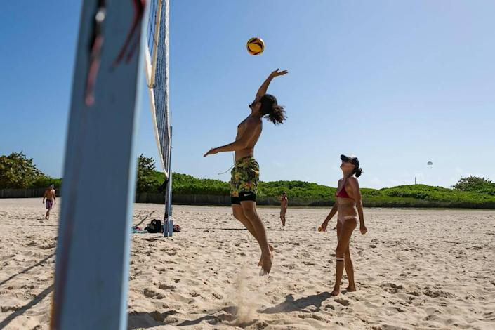 Gabriel Gonzalez, 22, and Bonnie Levin play volleyball at Lummus Park in Miami Beach, Florida on Monday, February 15, 2021.