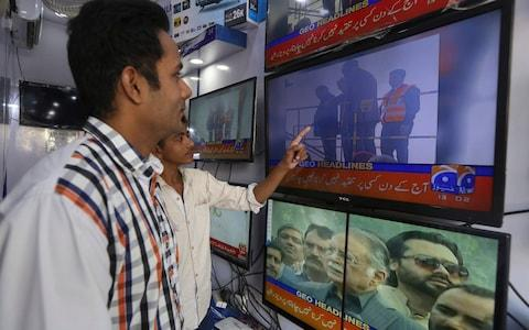 People watch television news showing the departure of Pakistan's ailing former Prime Minister Nawaz Sharif in Karachi, Pakistan, Tuesday, Nov. 19, 2019.  - Credit: AP
