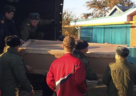 Russian servicemen unload a coffin containing the body of Vadim Kostenko, one of the Russian air force's support staff in Syria, from a truck near his family's house in the village of Grechnaya Balka, north-west of Krasnodar, Russia, October 27, 2015. The body of the first Russian serviceman confirmed dead in four weeks of air strikes in Syria was delivered on Tuesday to his parents, who said they were not convinced by the military's account that their 19-year-old son had hanged himself. In an interview with Reuters at their home in southern Russia before they received the body of their son Vadim, Alexander and Svetlana Kostenko said their son had sounded cheerful over the phone as recently as Saturday, the day he died while working at an air base on the Syrian coast. REUTERS/Maria Tsvetkova