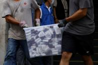 Movers collect a box of lotion after police search a warehouse of Student Politicism, in Hong Kong