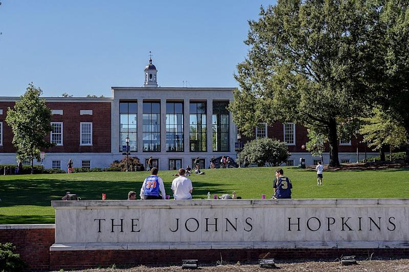 "A view from Charles street of the grassy ""Beach"" and Milton S Eisenhower Library of the Johns Hopkins University; three male students, their backs facing the camera, sit on top of the marble university sign, other students sunbathing and playing catch on the grassy hill; the clock tower of Gilman Hall, a humanities building, peeks above the top of the library; Baltimore, Maryland, March, 2014. Courtesy Eric Chen. (Photo by JHU Sheridan Libraries/Gado/Getty Images)."