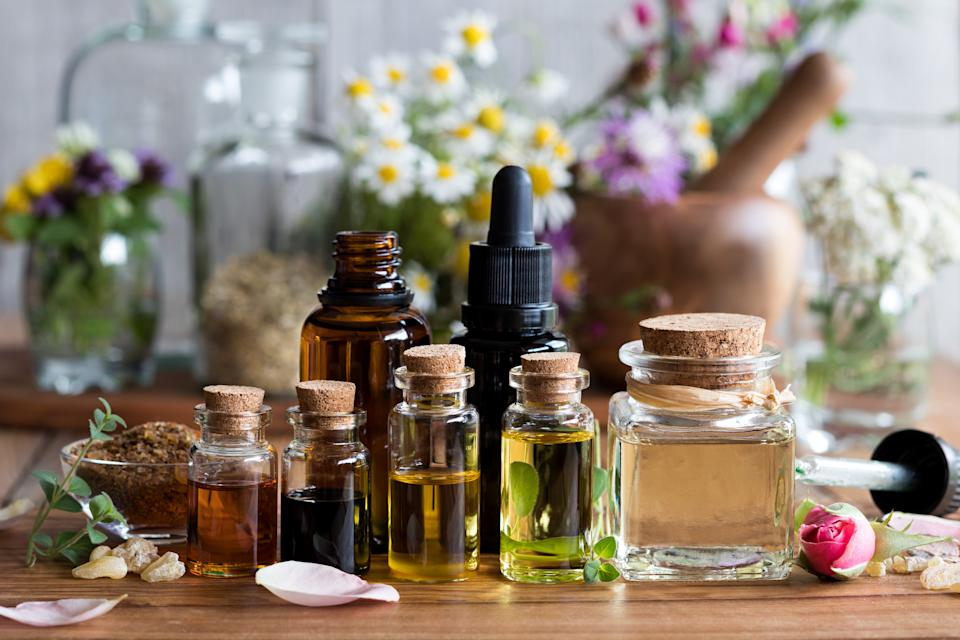 Selection of essential oils with various herbs and flowers in the background