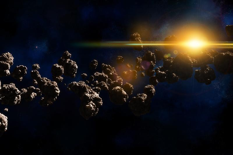 Filed of asteroids with space background and glowing orange shiny star.