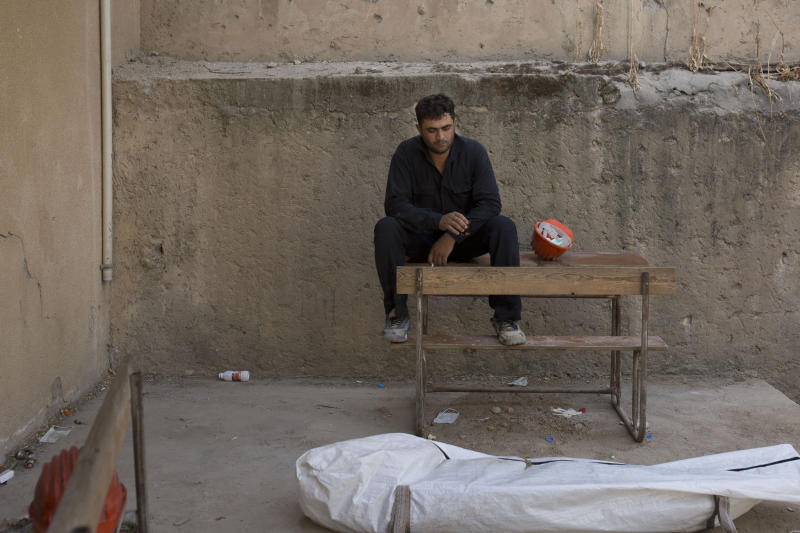 In this Saturday, Sept. 7, 2019 photo, a first responders takes a break after removing a body at the site of a mass grave in Raqqa, Syria. First responders say they have pulled nearly 20 bodies out of the latest mass grave uncovered in Raqqa, the Syrian city that was the de facto capital of the Islamic State group. It is the 16th mass grave in the city, and officials are struggling with a lack of resources needed to document and one day identify the thousands of dead who have been dug out. (AP Photo/Maya Alleruzzo)