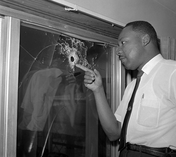 <p>Integration leader Dr. Martin Luther King looks at a glass door of his rented beach cottage in St. Augustine, Fla. that was shot into by someone unknown on June 5, 1964. King took time out from conferring with St. Augustine integration leaders to inspect the house, which no one was in at the time of the shooting. (AP Photo/Jim Kerlin) </p>