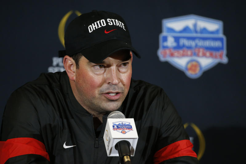Ryan Day in a black shirt and black Ohio State hat at a media conference.