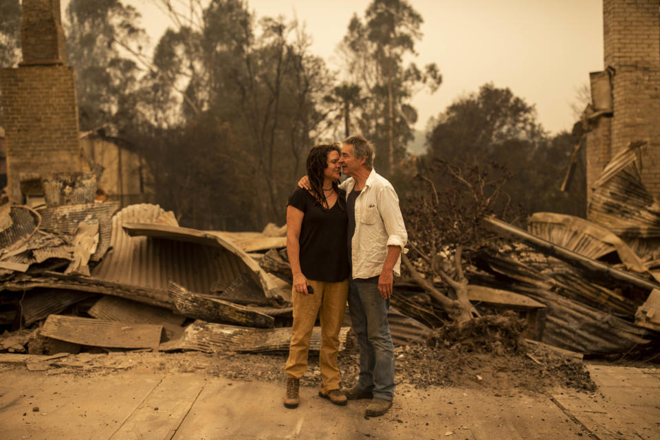 Business owner Sally Anne Wilson (left) stands in front of her destroyed shop with her partner Christopher Lee in Cobargo.
