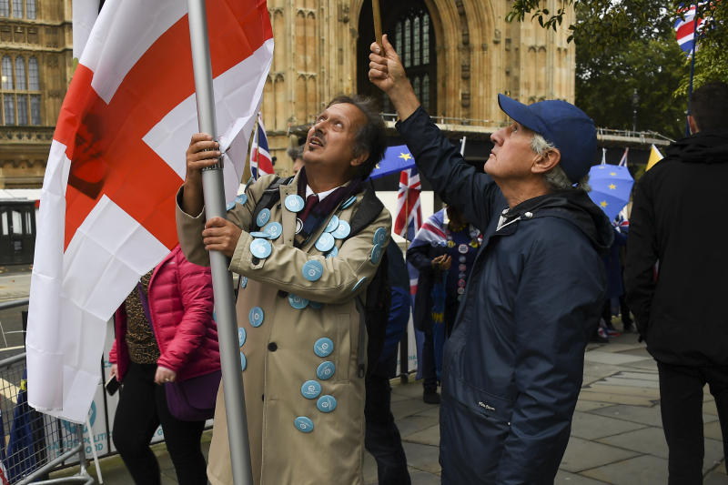 A pro-Brexit demonstrator holds an English flag outside the houses of Parliament, in London, Monday, Oct. 14, 2019.(AP Photo/Alberto Pezzali)