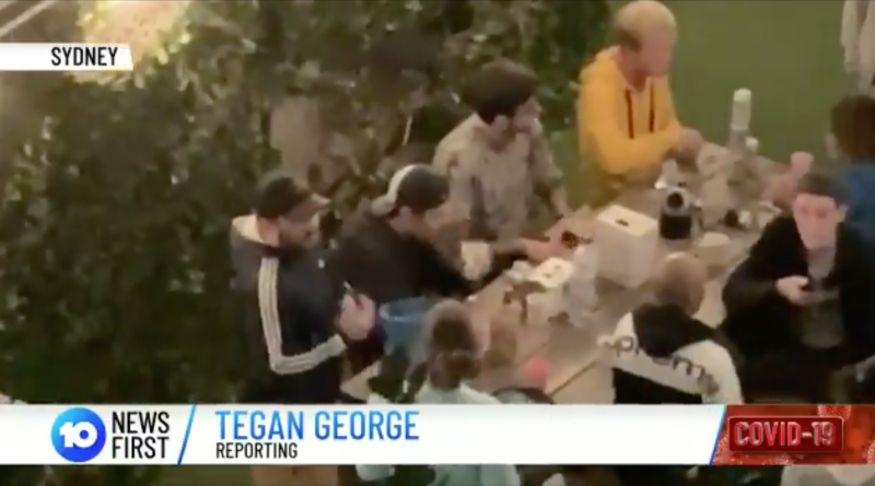A man films backpackers sitting next to each other as social-distancing rules apply to large gatherings. Source: 10 News First