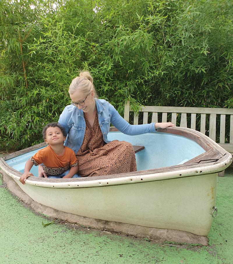 Hayley sitting in an old boat in the grass with her son.