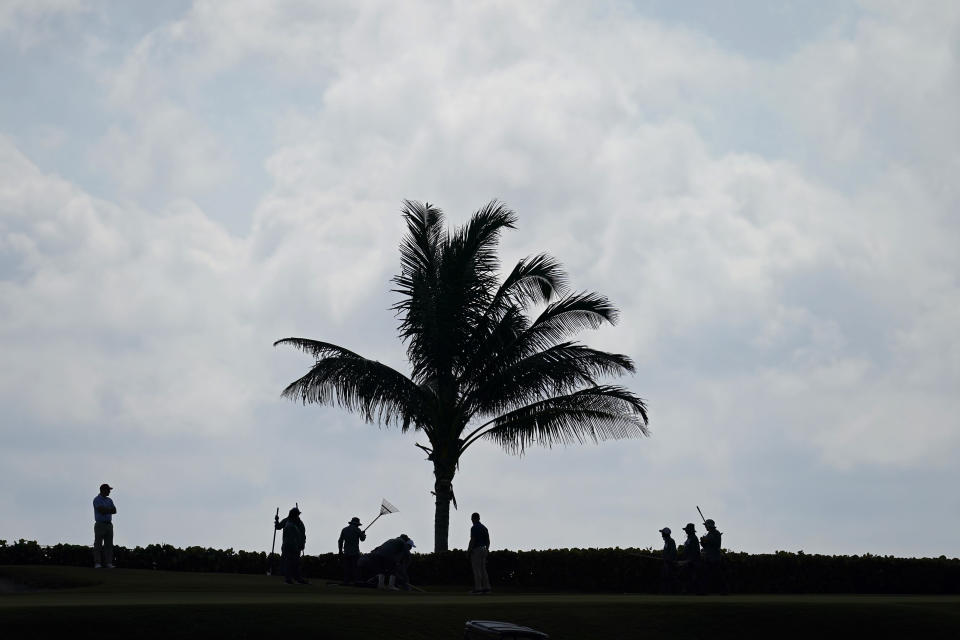 Workers groom the course after heavy thunderstorms moved through yesterday, on a practice day for the Walker Cup golf tournament at Seminole Golf Club in Juno Beach, Fla., Friday, May 7, 2021. (AP Photo/Gerald Herbert)