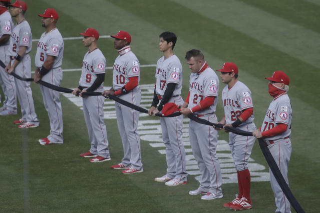 Los Angeles Angels' Andrelton Simmons, from left, Albert Pujols, Tommy La Stella, Justin Upton, Shohei Ohtani, Mike Trout, David Fletcher and manager Joe Maddon hold a black ribbon in honor of the Black Lives Matter movement with teammates and the Oakland Athletics before baseball game between the Athletics and the Angels in Oakland, Calif., Friday, July 24, 2020. (AP Photo/Jeff Chiu)