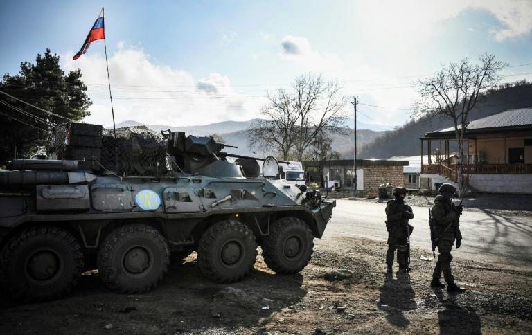 Russian peacekeepers stand beside a BTR-80 armoured vehicle at their checkpoint in the village of Chapar outside the town of Kalbajar