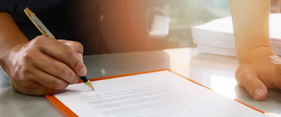 Close up of business man signing contract making a deal, business contract details. Businessman signing an official document