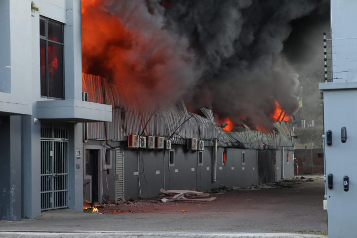 A factory burns on the outskirts of Durban, South Africa, Wednesday, July 14, 2021 in ongoing unrest. Rioting has continued which was sparked by the imprisonment last week of ex-President Jacob Zuma resulting in days of looting in two of the country's nine provinces. (AP Photo)
