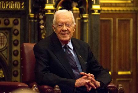 FILE PHOTO - Former U.S. President Jimmy Carter sits after delivering a lecture on the eradication of the Guinea worm, at the House of Lords in London, Britain