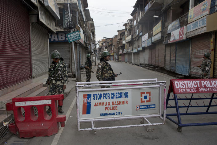 In this Tuesday, Aug. 6, 2019 photo, Indian Paramilitary soldiers stand guard during curfew in Srinagar, Indian controlled Kashmir, Wednesday, Aug. 7, 2019. Authorities in Hindu-majority India clamped a complete shutdown on Kashmir as they scrapped the Muslim-majority state's special status, including exclusive hereditary rights and a separate constitution, and divided it into two territories. (AP Photo/Dar Yasin)